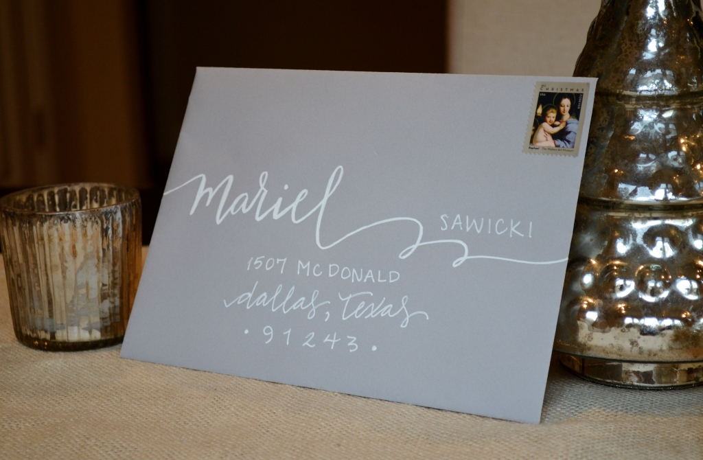 grey envelope with white lettering calligraphy from one charming life